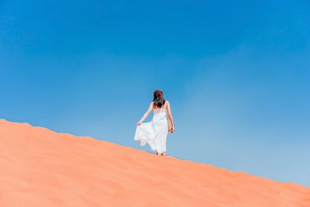 A young woman posing on the ridge of a red sand dune with a blue sky background.